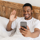 African Guy Making Video Call On Smartphone Lying In Bed - PhotoDune Item for Sale
