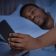 Guy Reading Message On Phone Lying In Bed At Night - PhotoDune Item for Sale