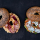 Two different bagels with lox and bacon on a black plate in dark setting - PhotoDune Item for Sale