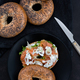 Salmon Lox Bagel with cream cheese and veggies on a dark setting - PhotoDune Item for Sale