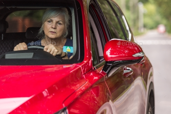 Old lady behind the wheel of a luxury red car - Stock Photo - Images