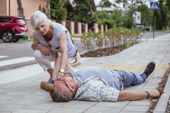 Helpful passerby checks the vital functions of the person who fainted on the street - Stock Photo - Images