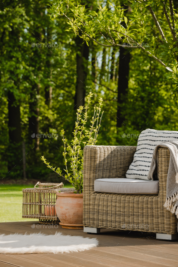 Wicker armchair with pillow on green terrace in beautiful garden - Stock Photo - Images