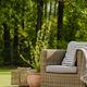 Wicker armchair with pillow on green terrace in beautiful garden - PhotoDune Item for Sale