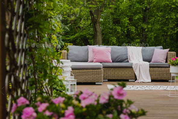 Pastel pink pillows on grey sofa in green garden with wooden terrace - Stock Photo - Images