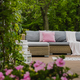 Pastel pink pillows on grey sofa in green garden with wooden terrace - PhotoDune Item for Sale