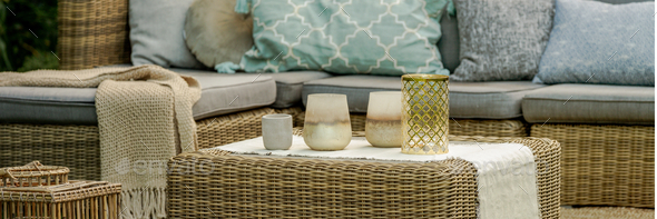Lanterns, candles and vases on wicker coffee table in front of garden sofa - Stock Photo - Images