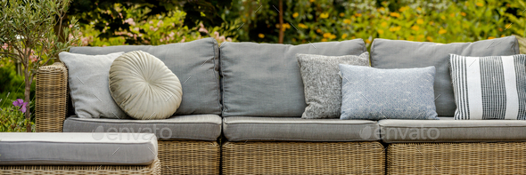 Grey pillows on trendy wicker L shape sofa in the green garden - Stock Photo - Images