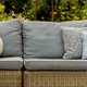 Grey pillows on trendy wicker L shape sofa in the green garden - PhotoDune Item for Sale