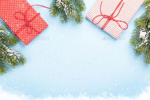 Christmas gift boxes and fir tree over blue background - Stock Photo - Images