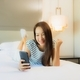Portrait beautiful young asian woman use smart mobile phone on bed - PhotoDune Item for Sale