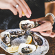 Woman squeezing lemon juice to fresh Irish oysters - PhotoDune Item for Sale