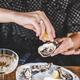 Woman squeezing lemon juice to fresh Irish oysters in restaurant - PhotoDune Item for Sale