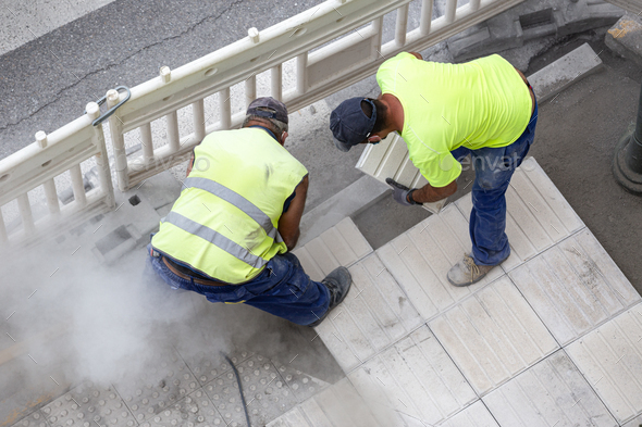 Construction workers repairing a sidewalk - Stock Photo - Images