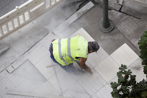 Construction worker with angle grinder repairing a sidewalk - Stock Photo - Images
