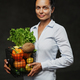 Portrait of a happy middle-aged woman in apron holds a basket of fresh vegetables and fruit - PhotoDune Item for Sale