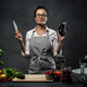 Beautiful mature woman cooking in kitchen, posing holding a knife and eggplant - PhotoDune Item for Sale