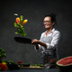 Beautiful mature woman cooking vegetable salad in the kitchen, tosses vegetables from the pan - PhotoDune Item for Sale