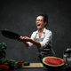 Emotional mature female chef tossing chopped vegetables from a pan - PhotoDune Item for Sale