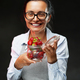 Beautiful middle-aged woman holds a glass with ripe juicy strawberry, smiling and looking on camera - PhotoDune Item for Sale