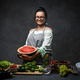 Middle-aged female chef holds half the watermelon in kitchen, smiling and looking on the camera - PhotoDune Item for Sale