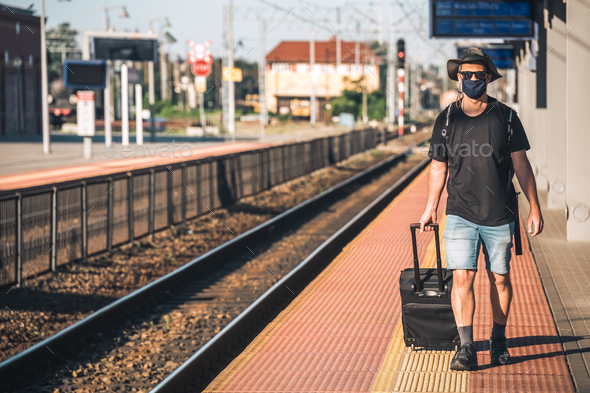Man with a mask waiting for a train during Covid19 pandemic - Stock Photo - Images