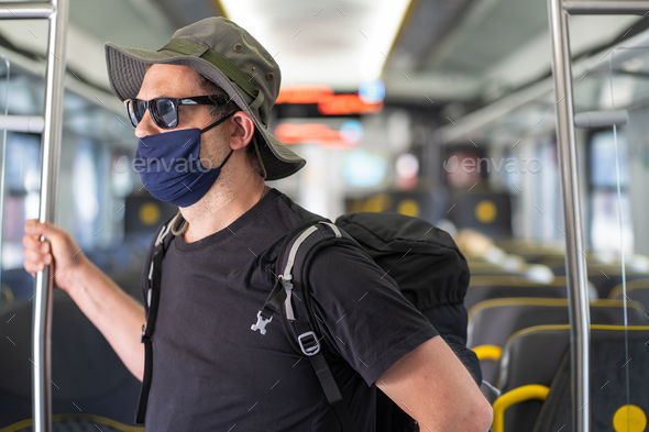 Man with a mask talking traveling in the train during Covid19 pandemic - Stock Photo - Images