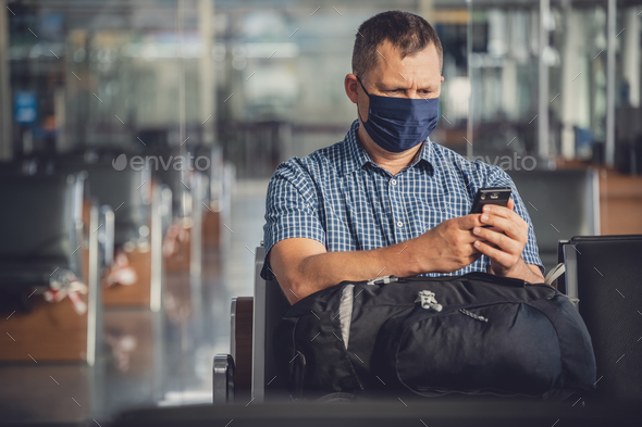 Man with a mask talking on mobile phone in airport lounge - Stock Photo - Images