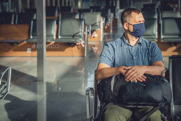 Man with a backpack waiting for departure in Covid19 time - Stock Photo - Images
