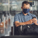 Man with a mask talking on mobile phone in airport lounge - PhotoDune Item for Sale