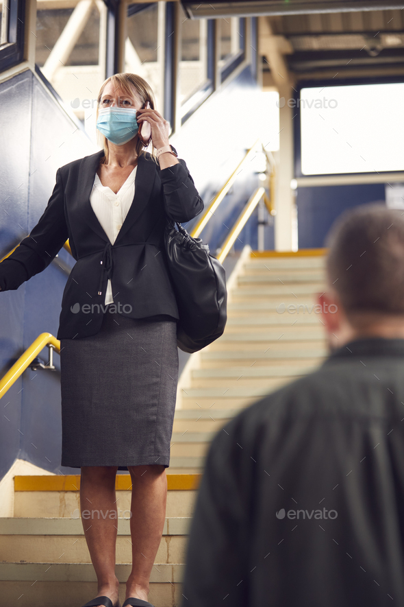 Businesswoman At Railway Station Talks On Mobile Phone Wearing PPE Face Mask During Health Pandemic - Stock Photo - Images