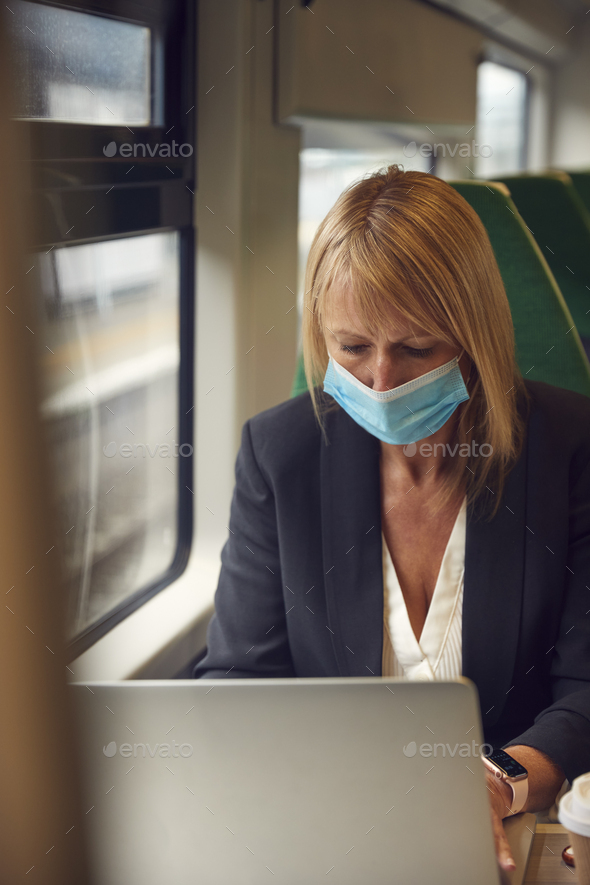 Businesswoman On Train Working On Laptop Wearing PPE Face Mask During Health Pandemic - Stock Photo - Images