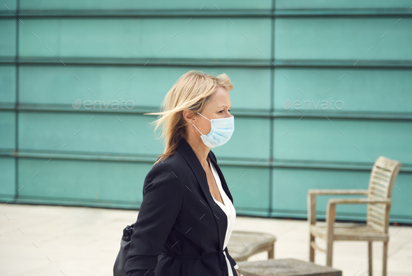 Mature Businesswoman Wearing PPE Face Mask Walking Outdoors In Street During Health Pandemic - Stock Photo - Images