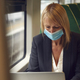 Businesswoman On Train Working On Laptop Wearing PPE Face Mask During Health Pandemic - PhotoDune Item for Sale