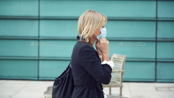 Mature Businesswoman Putting On PPE Face Mask Walking Outdoors In Street During Health Pandemic - Stock Photo - Images