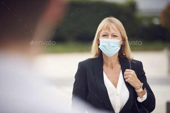 Mature Businesswoman Wearing PPE Face Mask Meeting Colleague In Street During Health Pandemic - Stock Photo - Images