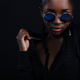 Confident and cool woman with dark skin wearing round sunglasses - PhotoDune Item for Sale