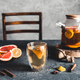 Citrus tea in a transparent teapot on a gray concrete background. Healthy drink, vegan, eco product - PhotoDune Item for Sale