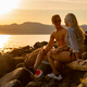 Happy Young Couple Sitting On Rocks Enjoying Beer At Beach - PhotoDune Item for Sale