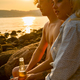 Couple relaxing and drinking beer at the beach at sunset - PhotoDune Item for Sale