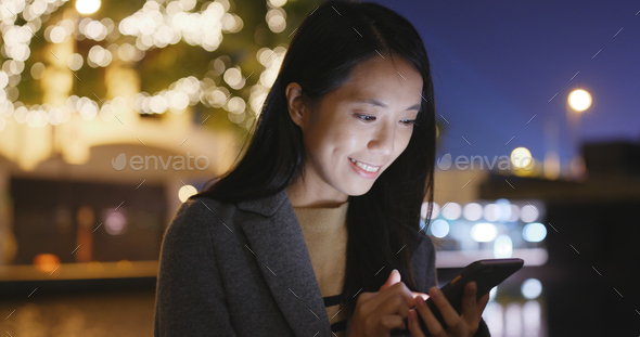 Woman uses a cellphone in city at night - Stock Photo - Images