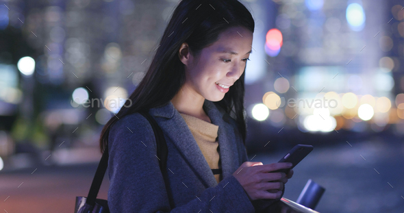Asian Woman use of smart phone in city at night - Stock Photo - Images