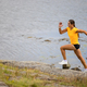 Focused fitness woman doing high-intensity running on mountainside by the sea - PhotoDune Item for Sale