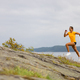 Side view of fitness woman doing high-intensity running on mountainside by the sea - PhotoDune Item for Sale