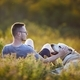 Man with dog lying on meadow at sunset - PhotoDune Item for Sale