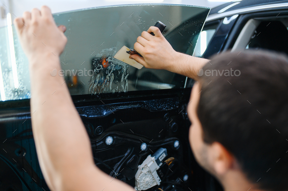 Worker installs wetted car tinting, tuning service - Stock Photo - Images