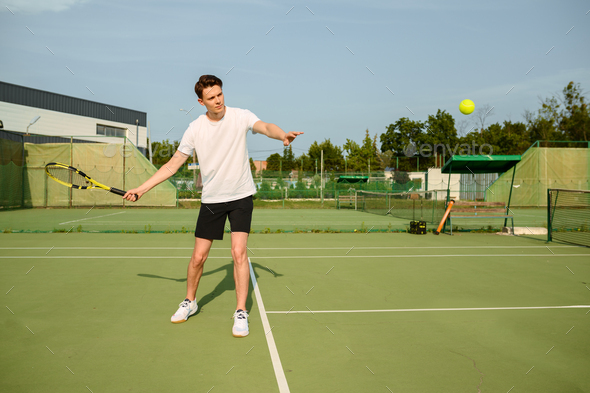 Male tennis player with racket hits the ball - Stock Photo - Images