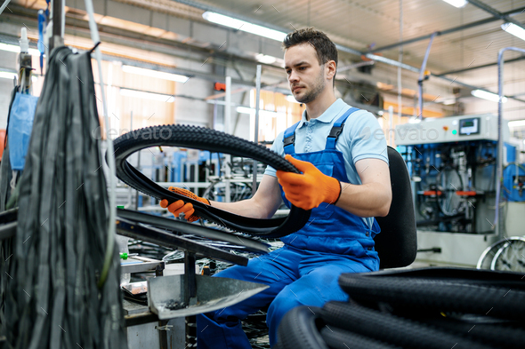 Worker at the assemly line holds bicycle tire - Stock Photo - Images