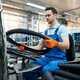 Worker at the assemly line holds bicycle tire - PhotoDune Item for Sale