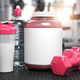 Pink whey protein can with pink dumbbell sand shaker on the floor of gym. Mock up. - PhotoDune Item for Sale